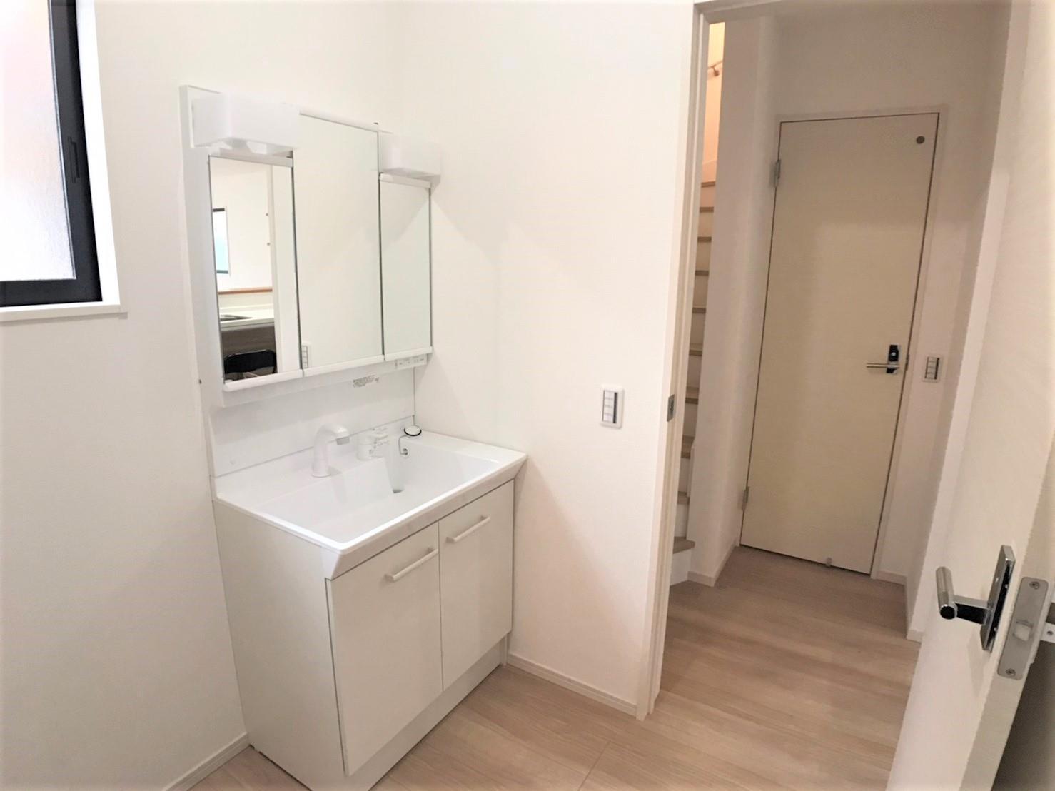 洗面台・洗面所1号棟・洗面化粧室  ●清潔感ある洗面化粧室です。化粧台は使いやすい三面鏡タイプを採用!鏡の裏側、足元の扉も収納スペースになっています。洗剤、お風呂の掃除用具など収納できます♪