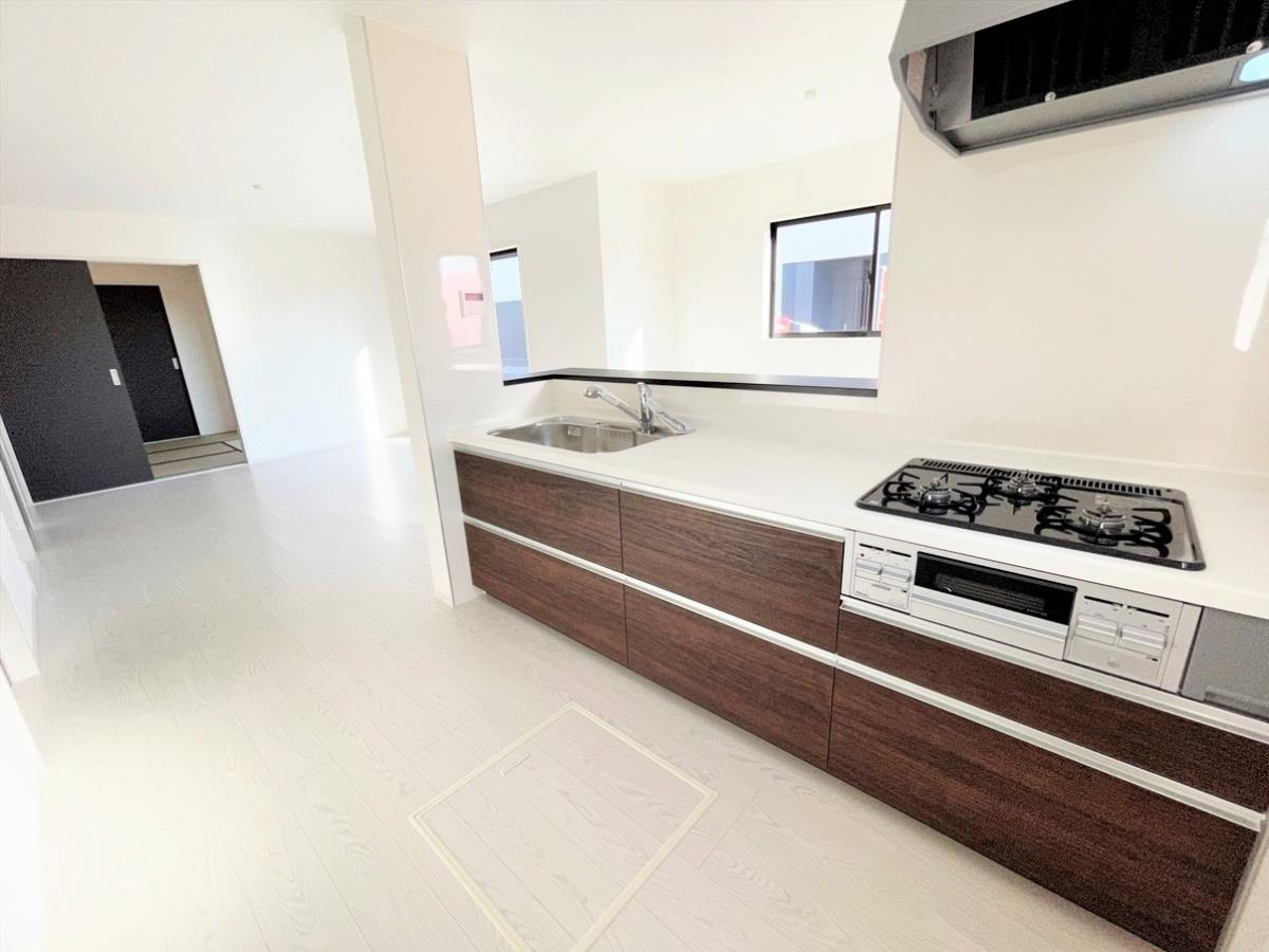 1号棟|キッチンイメージ※同仕様施工例|大きな鍋やフライパンを収納できるスライド収納が完備されています。また、カウンターが広いので作業がしやすく、シンクやコンロなどのお手入れがしやすい仕様です。