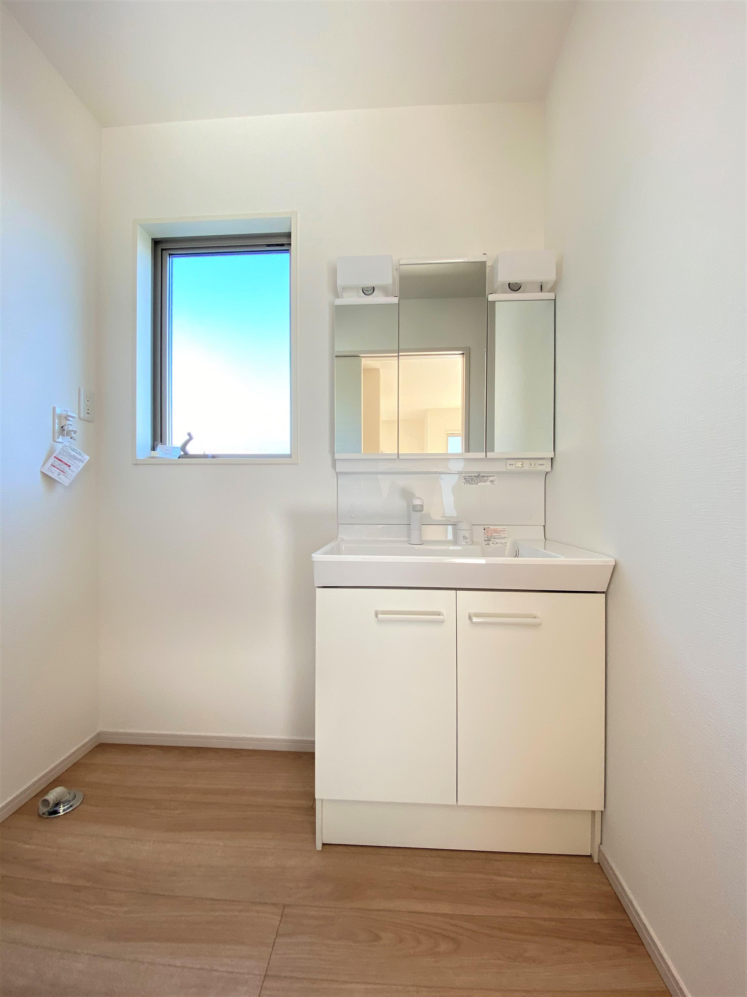 洗面台・洗面所2号棟|洗面脱衣所には使いやすい三面鏡の洗面台を設置しました。鏡の裏側には便利な収納スペースもついており、使いやすい仕様です。
