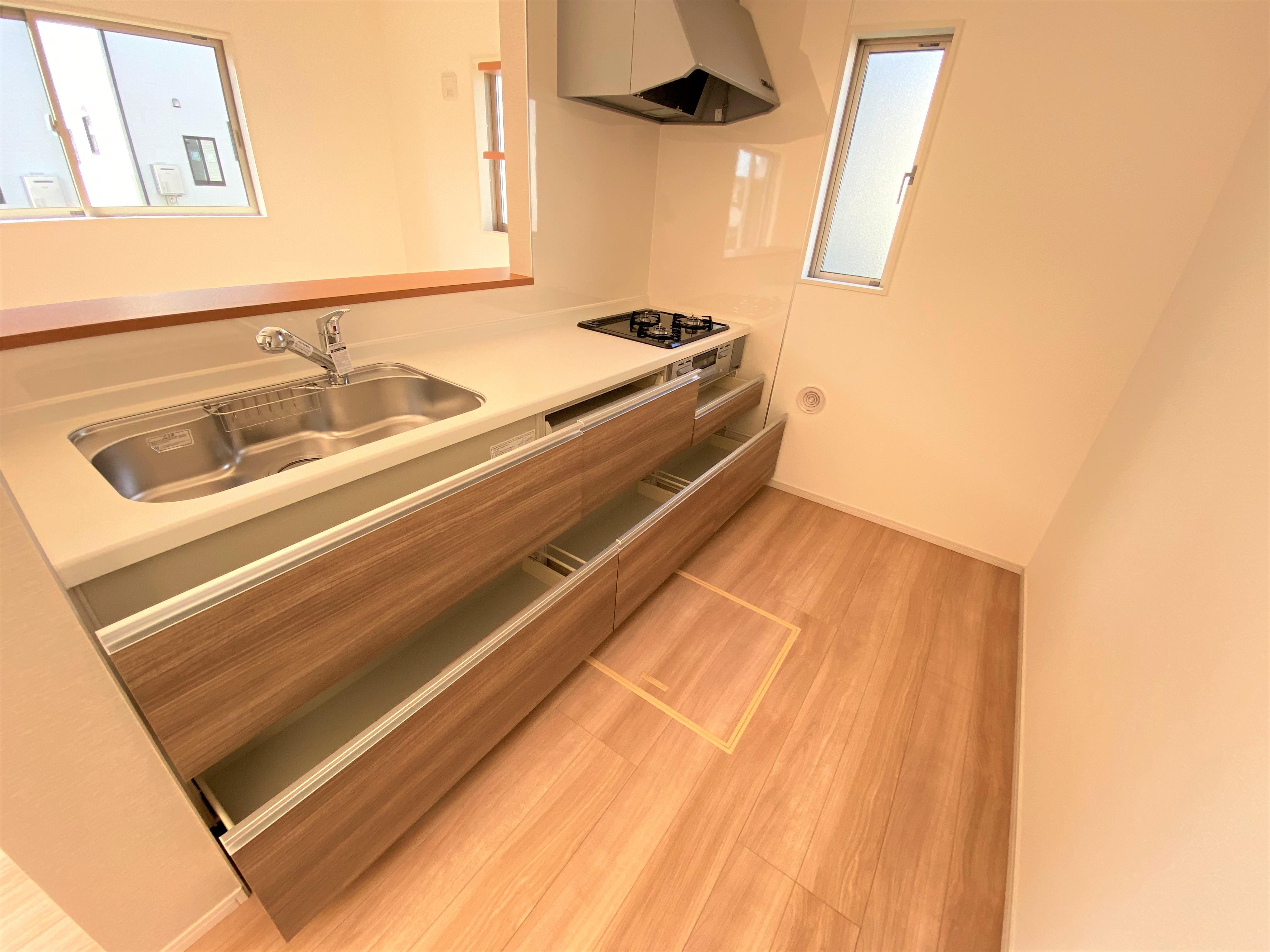 2号棟|広々と使いやすい調理スペースのキッチン。鍋やフライパンなどすっぽりしまえる大容量のスライド収納付きです。忙しいママの強い味方です。