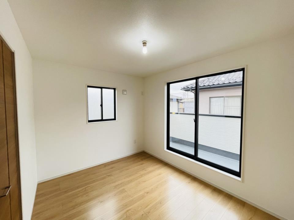 6.5帖の洋室。窓が複数あり、風通しの良い清潔感のあるお部屋です。白い壁で間接的に部屋を明るくする工夫をしています。